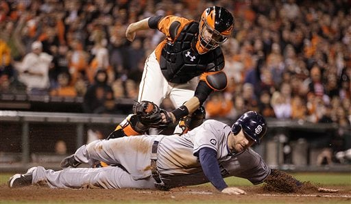 © San Diego Padres' Chase Headley is tagged out at home plate by San Francisco Giants catcher Buster Posey (top) in the sixth inning of a baseball game Friday, Sept 21, 2012, in San Francisco. Headley attempted to score on a double by Yasmani Grandal.