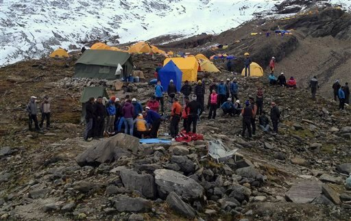 In this photo provided by Nepalese airline Simrik Air, rescuers attend to injured victims, unseen, after an avalanche at the base camp of Mount Manaslu in northern Nepal, Sunday, Sept. 23, 2012. (AP Photo/Simrik Air)