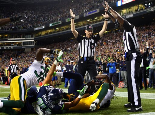 © Officials signal after Seattle Seahawks wide receiver Golden Tate pulled in a last-second pass for a touchdown from quarterback Russell Wilson to defeat the Green Bay Packers 14-12 in an NFL football game, Monday, Sept. 24, 2012, in Seattle.