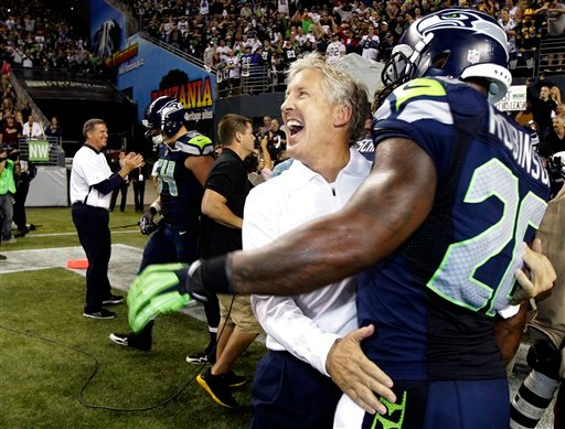 © Seattle Seahawks head coach Pete Carroll, second from right, celebrates with Seahawks' Michael Robinson after defeating the Green Bay Packers 14-12 an NFL football game, Monday, Sept. 24, 2012, in Seattle.