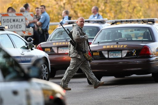 An officer walks through the area as police investigate a shooting at Accent Signage Systems on the north side of Minneapolis Thursday, Sept. 27, 2012. (AP Photo/The Star Tribune, Renee Jones Schneider)