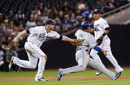 San Diego Padres third baseman Chase Headley puts the tag on Los Angeles Dodgers' Luis Cruz, who was caught in a rundown during the second inning of a baseball game Thursday, Sept. 27, 2012, in San Diego. (AP Photo/Lenny Ignelzi)