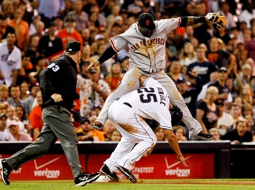© San Francisco Giants third baseman Pablo Sandoval lands on the elbow of San Diego Padres' Will Venable after failing to catch a wild throw from left field during the sixth inning of a baseball game Friday, Sept. 28, 2012 in San Diego.