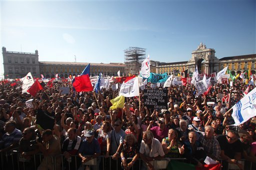 © Protestors fill Lisbon's Comercio Square during a workers unions' demonstration, Saturday, Sept. 29 2012. Thousands of Portuguese enduring deep economic pain from austerity cuts took to the streets Saturday in protest. (AP Photo/Joao Henriques)