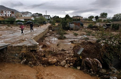 © Residents walk on a muddy street after heavy rain caused flash floods in the town of Villanueva del Rosario, Malaga, southern Spain, Friday, Sept. 28, 2012. Homes were destroyed and at least one woman was killed.