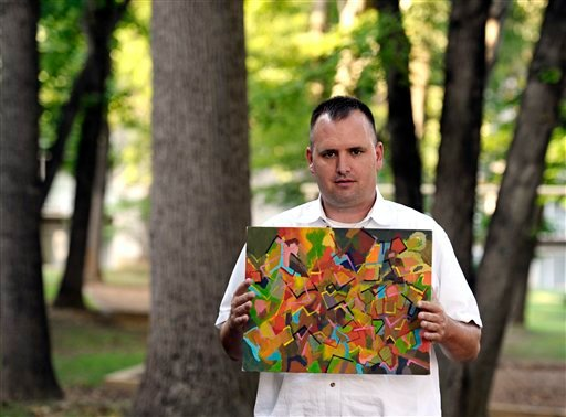 In this Aug. 23, 2012 photo, Kevin Earley, 33, displays one of his paintings outside his Vienna, Va., apartment that he shares with a roommate. (AP Photo/Cliff Owen)