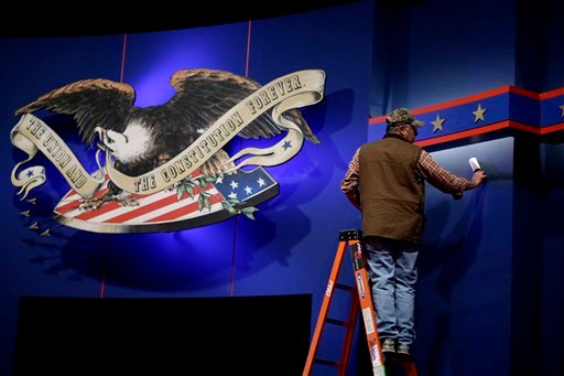 A worker cleans lint off the background of the stage for a debate at the University of Denver ,Tuesday, Oct. 2, 2012, in Denver. (AP Photo/David Goldman)
