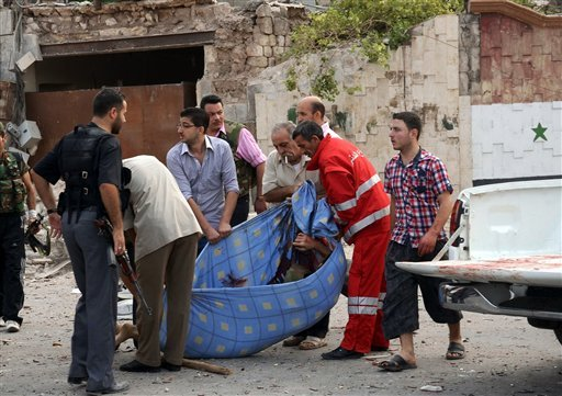 In this photo released by the Syrian official news agency SANA, Syrian men carry a dead body at the scene where triple bombs exploded at the Saadallah al-Jabri square, in Aleppo city, Syria.