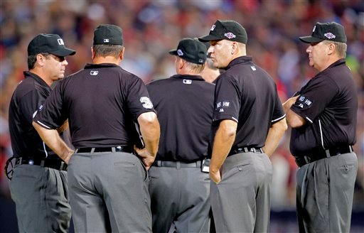 © Officials stand in the center of the field as fans throw trash during the eighth inning of the National League wild card playoff baseball game between the Atlanta Braves and the St. Louis Cardinals, Friday, Oct. 5, 2012, in Atlanta.