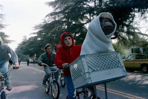 "© This undated publicity film image released by Universal Pictures shows Henry Thomas as Elliott and E.T. in a basket on a bicycle in a scene from director Steven Spielberg's ""E.T.: The Extra-Terrestrial."""
