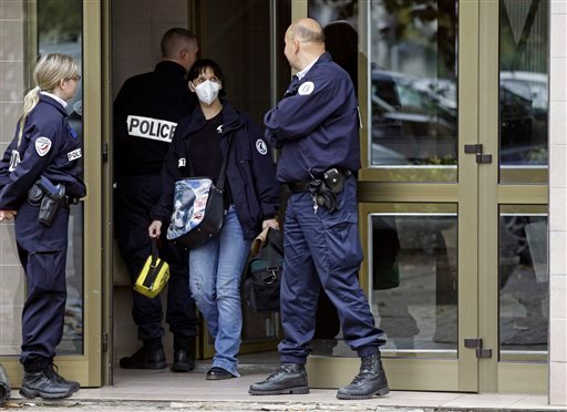 © French police officers stand guard at the entrance of a building in Strasbourg, France, Saturday Oct. 6, 2012, where a suspect was shot dead after firing at police.