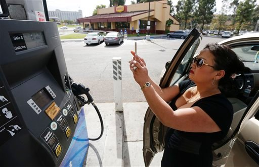© Lorena Delara takes a picture of the total she paid after filling up her tank with gasoline at a gas station Friday, Oct. 5, 2012, in San Diego.