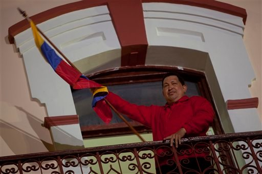 © Venezuela's President Hugo Chavez holds a Venezuelan flag as he greets his supporters from the Miraflores presidential palace balcony in Caracas, Venezuela, Sunday, Oct. 7, 2012.