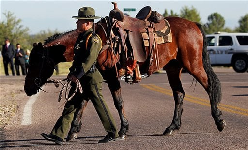 U.S. Border Patrol agent Nicholas Ivie's riderless horse with boots set backward in honor of the slain agent is seen during the funeral procession on Monday, Oct. 8, 2012. (AP Photo/Arizona Daily Star,Mike Christy)