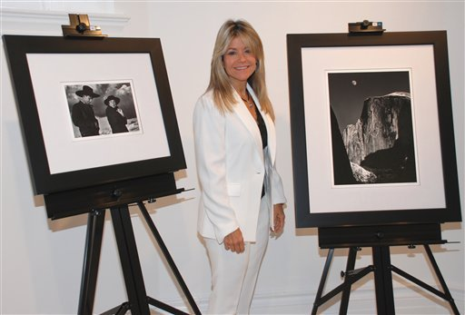 In this photo provided by the College of New Rochelle, Judith Huntington, president of The College of New Rochelle, is flanked by 2 Ansel Adams photographs at the school in New Rochelle Oct. 9, 2012. (AP Photo/College of New Rochelle)