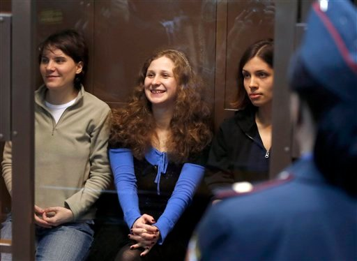 Feminist punk group Pussy Riot members, from left, Yekaterina Samutsevich, Maria Alekhina, and Nadezhda Tolokonnikova sit in a glass cage at a court room in Moscow Oct. 10, 2012. (AP Photo/Sergey Ponomarev)