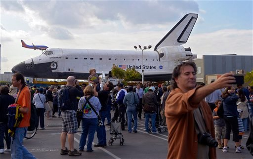 Spectators gather around the Space Shuttle Endeavour before it is moved along city streets, Friday, Oct.12, 2012, in Los Angeles. (AP Photo/Mark J. Terrill)