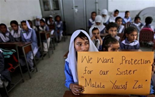Pakistani girls display a poster while sitting at their desk, as their teacher, not shown, talks to them about 14-year-old schoolgirl Malala Yousufzai. (AP Photo/Muhammed Muheisen)