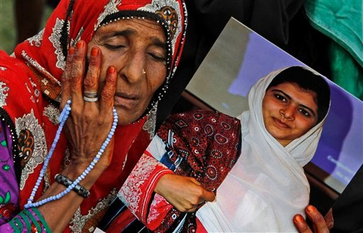 © A supporter of Pakistani political party Muttahida Qaumi Movement (MQM), reacts while holding a poster of 14-year-old schoolgirl Malala Yousufzai, who was shot last Tuesday by the Taliban for speaking out in support of education for women.