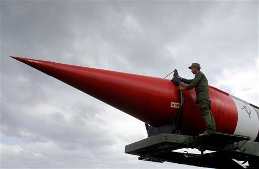 © A soldier poses for a photograph on the outer casing of an old, empty Soviet missile on exhibit at the military complex Morro Cabana which is open to tourists in Havana, Cuba, Saturday, Oct. 13, 2012.