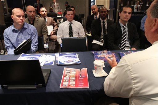 In this Friday Sept. 28, 2012, photo, a group of veterans listen as a representative from White Rose Foods, foreground right, talks about their agency during a job fair. (AP Photo/Tina Fineberg)