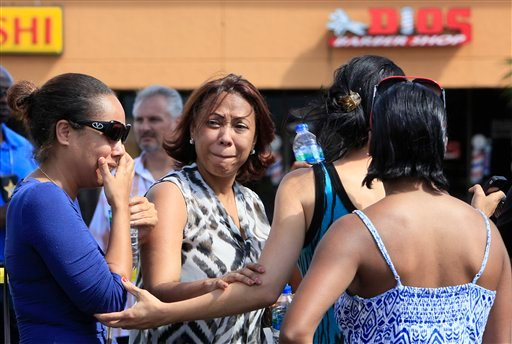 Family and friends gather at the scene of the shooting at Las Dominicanas M&M Salon in Winter Park, Fla., Thursday, Oct. 18, 2012. (AP Photo/Julie Fletcher)