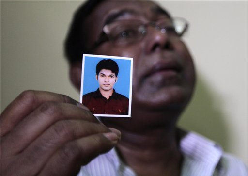 Bangladeshi Quazi Ahsanullah displays a photograph of his son Quazi Mohammad Rezwanul Ahsan Nafis as he weeps in his home in the Jatrabari neighborhood in north Dhaka, Bangladesh, Thursday, Oct. 18, 2012. (AP Photo/A.M. Ahad)