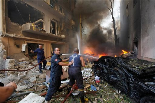 © Lebanese firefighters extinguish burning cars at the scene of an explosion in the mostly Christian neighborhood of Achrafiyeh, Beirut, Lebanon, Friday Oct. 19, 2012.