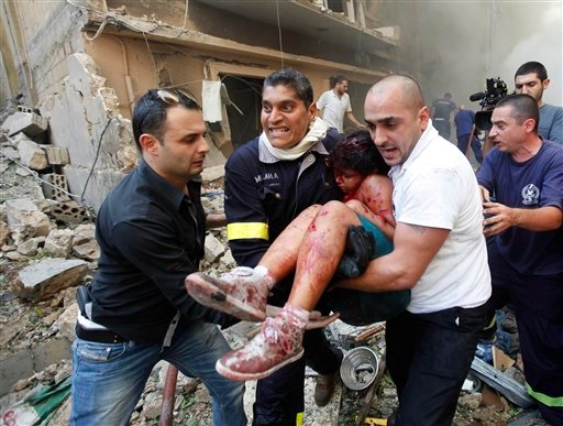 © Lebanese rescue workers and civilians carry an injured girl from the scene of an explosion in the mostly Christian neighborhood of Achrafiyeh, Beirut, Lebanon, Friday Oct. 19, 2012.