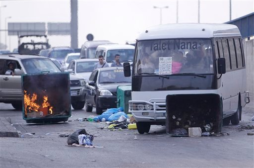 © A bus pushes a garbage container used as a roadblock by Sunni protesters after overnight clashes between Sunni and Shiite gunmen in Beirut, Lebanon, Monday Oct. 22, 2012.