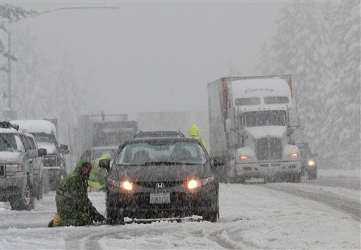 © Chain installers work as snow falls on eastbound Interstate 80 near Nyack, Calif., Monday, Oct. 22, 2012. The first storm of the season swept through Northern California bringing rain to the lower elevations and snow in the mountains.