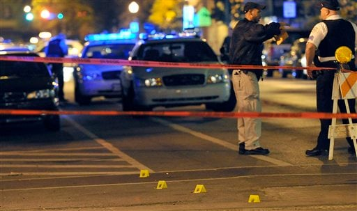 In this photo taken Oct. 2, 2012, police investigate the scene of a shooting in Chicago. In the coming days, the city is bound to reach another grim milestone when the number of homicides for 2012 surpasses 433, the total for all of last year. (AP Photo)