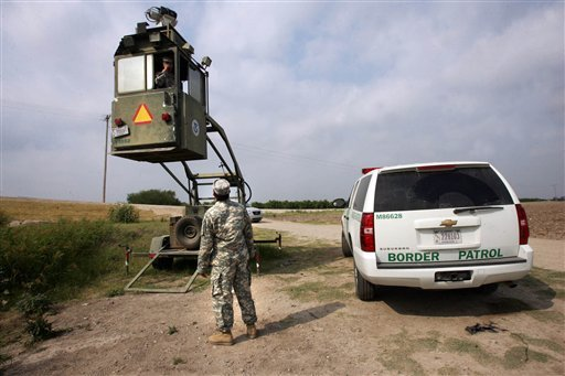 FILE - This April 19, 2011 file photo shows a member of the National Guard checking on his colleague inside a Border Patrol Skybox near the Hidalgo International Bridge in Hidalgo, Texas. (AP Photo/Delcia Lopez, File)