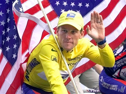 FILE - This July 23, 2000 file photo shows Tour de France winner Lance Armstrong riding down the Champs Elysees with an American flag after the 21st and final stage of the cycling race in Paris, France. (AP Photo)