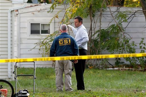 Investigators look in the rear yard of a home Tuesday, Oct. 23, 2012, in Clayton, N.J., after a body preliminarily identified as a missing 12-year-old girl's was found in a home's recycling bin. (AP Photo/Mel Evans)