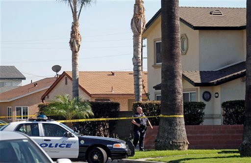 A police officer stands outside a two-story home, right, where one person was found shot to death in Downey, Calif., Wednesday, Oct. 24, 2012. (AP Photo/Nick Ut)