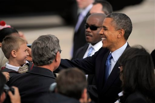 President Barack Obama greets and young boy, and other supporters, on the tarmac upon his arrival on Air Force One, Wednesday, Oct. 24, 2012, at Buckley Air Force Base in Aurora Colo. (AP Photo/Jack Dempsey)