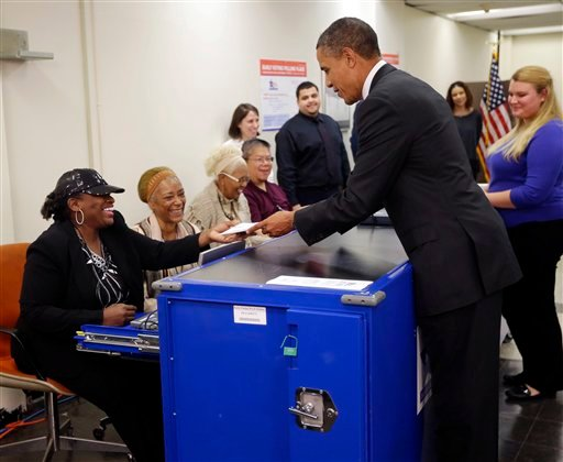 President Barack Obama, right, turns in his ballot receipt to election official Marie Holmes, left, as he prepares to cast his vote, during early voting, in the 2012 election at the Martin Luther King Community Center, Thursday, Oct. 25, 2012, in Chicago.