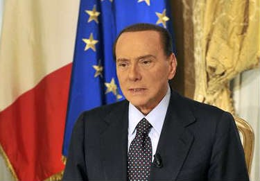 © In this photo released by the Berlusconi press office Thursday, Oct. 25, 2012, former Italian premier Silvio Berlusconi tapes a video message where he announces he will not run for a fourth term as premier in spring elections.