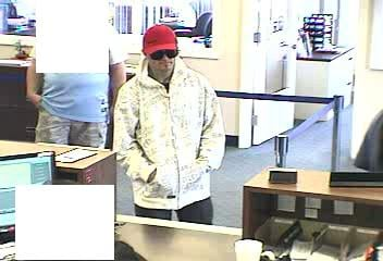 "© Bank surveillance photos show the suspect, described as a white male, approximately 30 years old, 5'5"" to 5'10"" tall and 160 lbs."