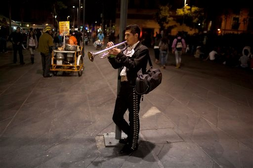 © In this Oct. 5, 2012 photo photo, professor at the Mariachi School Ollin Yoliztli, Eduardo Sanchez Ortiz, practices as he waits for clients at Plaza Garibaldi in Mexico City.