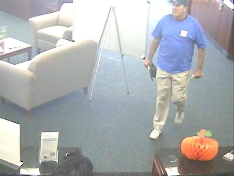 "© Bank surveillance photos show the suspect, described as a white male, 6'1"" tall, 230 lbs, approximately 45 to 50 years old."