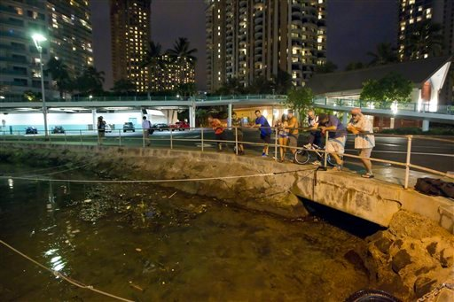 © Visitors and Oahu residents watch the water level in the Ala Wai Harbor waiting for the arrival of a tsunami Saturday, Oct. 27, 2012, in Honolulu.