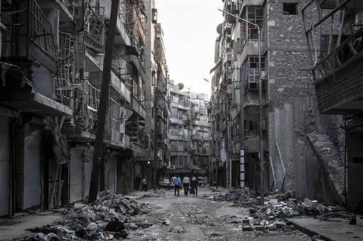 © In this Saturday, Oct. 27, 2012 photo, Syrian residents walk on a street among the debris of buildings damaged by heavy shelling in the southeast of Aleppo City. (AP Photo/Narciso Contreras).