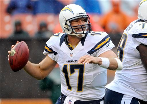 © As rain falls, San Diego Chargers quarterback Philip Rivers rolls out to pass in the third quarter of an NFL football game against the Cleveland Browns, Sunday, Oct. 28, 2012, in Cleveland. (AP Photo/Phil Long)