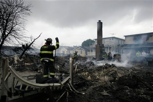 A fire fighter surveys the smoldering ruins of a house in the Breezy Point section of New York, Tuesday, Oct. 30, 2012. (AP Photo/Mark Lennihan)