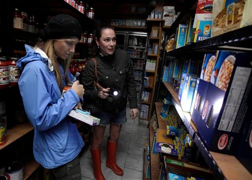 Two women shop for groceries by flashlight in the Tribeca neighborhood of New York, Tuesday, Oct. 30, 2012. (AP Photo/Richard Drew)