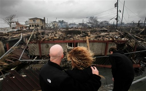 Robert Connolly, left, embraces his wife Laura as they survey the remains of the home owned by her parents that burned to the ground in the Breezy Point section of New York, Tuesday, Oct. 30, 2012. (AP Photo/Mark Lennihan)