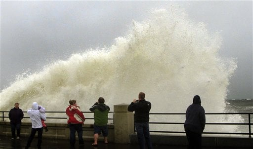 People watch waves crash in Hampton, N.H., from the effects of Hurricane Sandy Monday, Oct. 29, 2012. (AP Photo/Jim Cole)