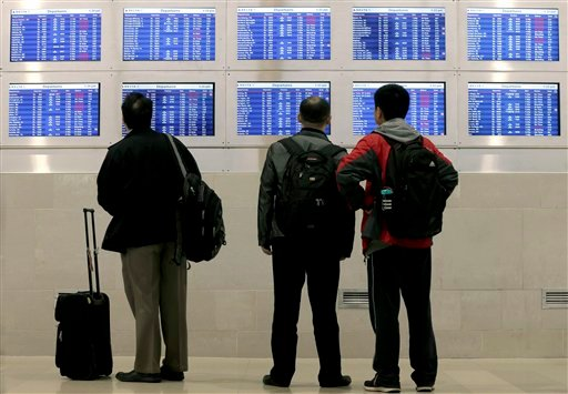 Travelers on Delta Airlines look at a departure screen Monday, Oct. 29, 2012, in Detroit. (AP Photo/Charlie Riedel)